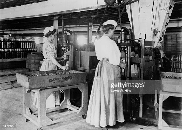Two women filling and capping jars of mustard in a mustard factory Pittsburgh Pennsylvania Both women are wearing bonnets and full aprons and skirts