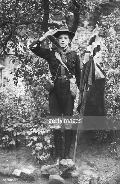 A Boy scout dressed in full uniform saluting next to an British flag