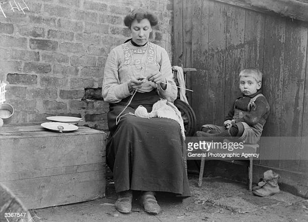 A child sits quietly as his mother knits Shetland wool into jumpers Wool was traditionally handspun and knitted into thick clothes in the Shetlands...