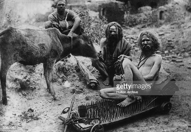 A Hindu fakir sitting on a bed of nails with other holy men or sadhu at Benares a holy place on the river Ganges India