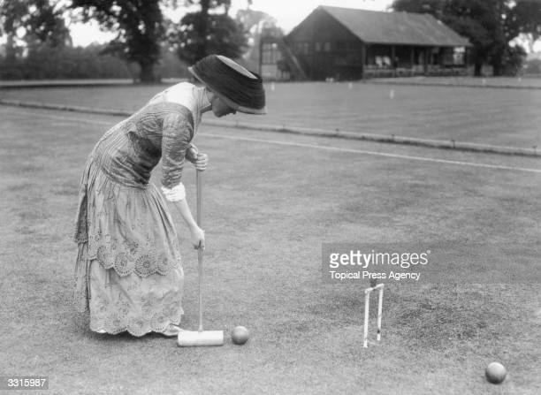A woman playing croquet