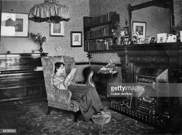 An Edwardian sitting room showing a woman reading in an armchair by the fireplace