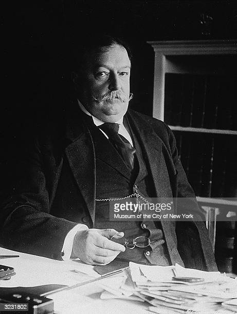 Portrait of American president William H Taft sitting at a desk, holding a pair of glasses in his hand.