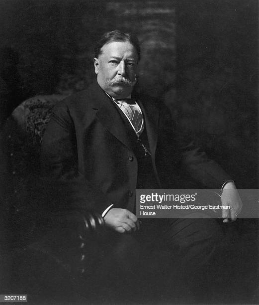 Portrait of American president William Howard Taft sitting in an armchair in a three-piece suit.