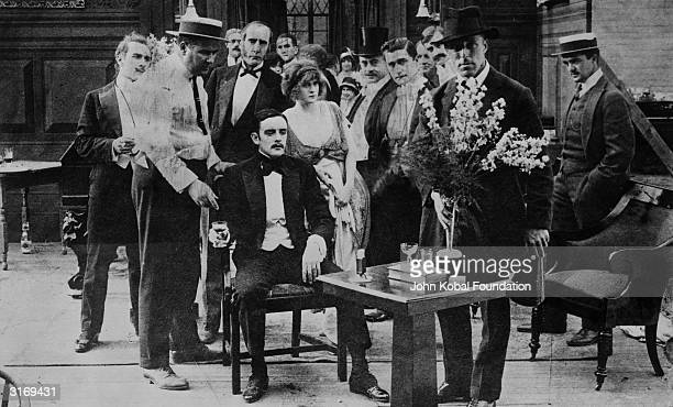 Prolific and influential American film maker, D. W. Griffith holds a vase of flowers on the set of one of his early films.