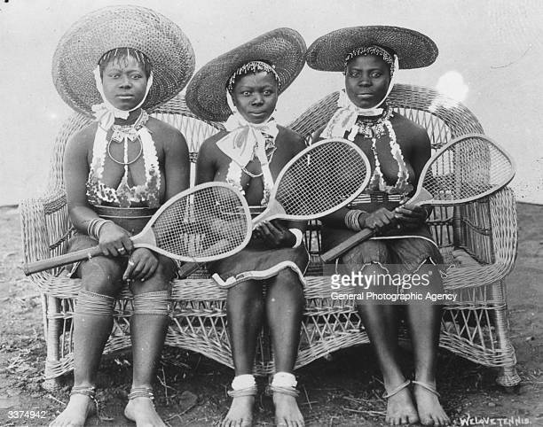 Three Zulu girls wearing large straw hats and holding tennis rackets