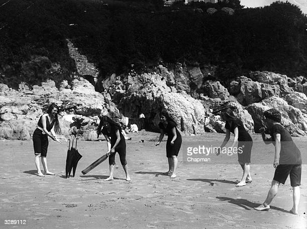 Young women play cricket on the beach at Swansea