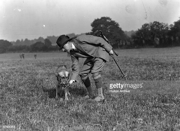 The Earl of Granard retrieves his dog and its prize at a partridge shoot at Shatton Park Hants He is carrying a shooting stick in his other hand