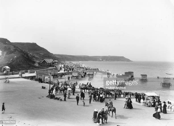 Daytrippers on the North Beach at Scarborough circa 1913 where they are offered rides bathing machines and a souvenir stall as well as the beach...
