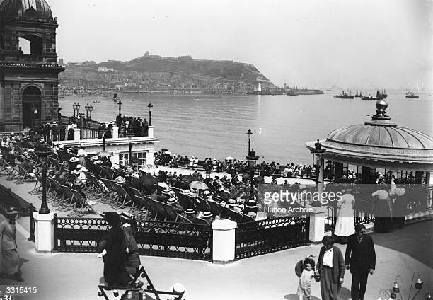 Holiday crowds listen to the band playing in the bandstand at the Spa, Scarborough, North Yorkshire.