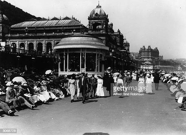 Tourists crowd the promenade near the bandstand at the North Yorkshire coastal resort of Scarborough