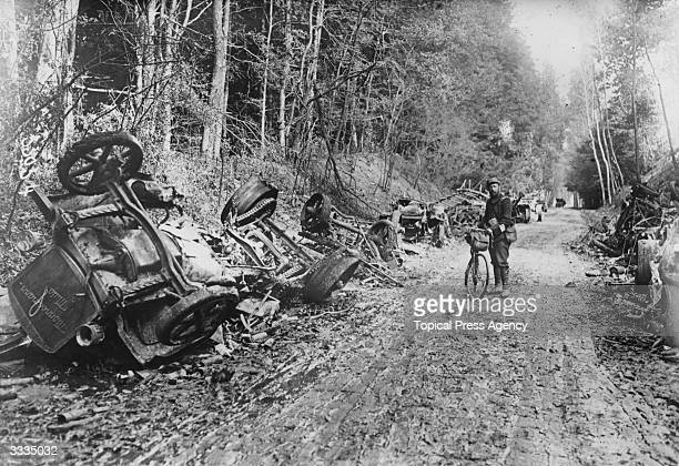 A lone soldier with a bicycle stands amid the remains of a German motor convoy which lines a country lane after an attack by French field guns in the...