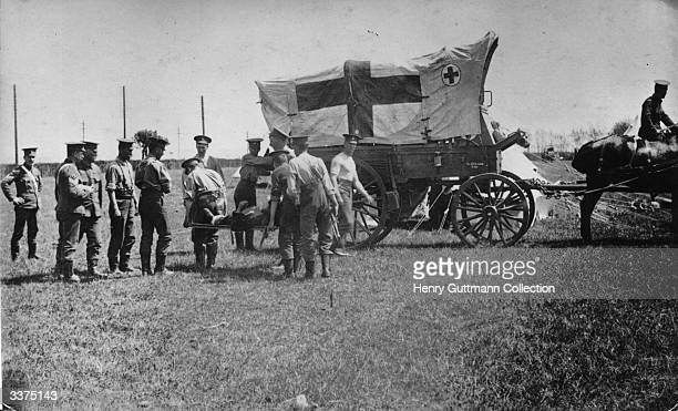 A stretcher being carried to a horsedrawn English ambulance during WW1