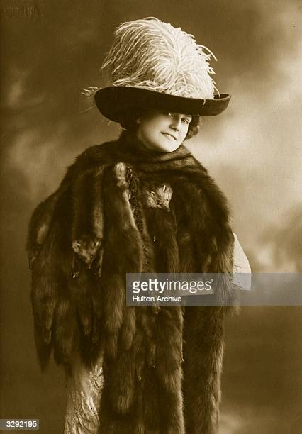Woman wearing a stole of mink furs, and an ostrich feather hat.