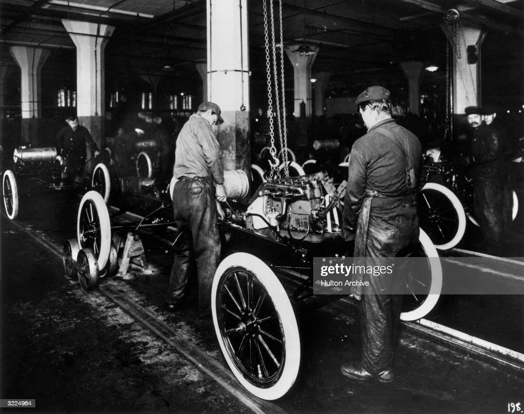 Workers Constructing A Model T Engine On An Assembly Line In Ford Motor Company