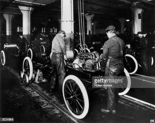 Workers constructing a ModelT engine on an assembly line in a Ford Motor Company factory