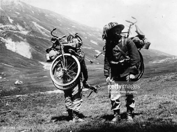 A couple of soldiers from the Italian Rifle Battalion carrying their bicycles on their backs as they walk up a hill