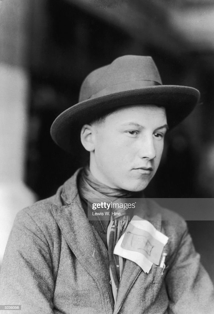 A headshot of an immigrant boy wearing a suit jacket, scarf and hat, with a tag affixed to his chest, Ellis Island, New York City..