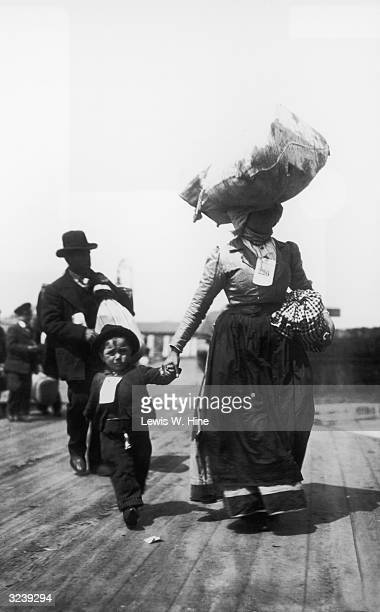 Mother, father, and young son walk on the pier upon their arrival at Ellis Island, New York City. The mother carries a bag of luggage on her head and...