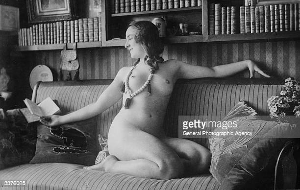 A nude woman relaxes with a book on her sofa