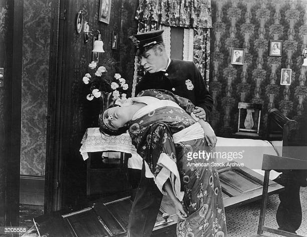 A policeman holds a woman after she fainted in his arms inside an apartment in an unidentified silent film still The woman wears an Asian robe and a...