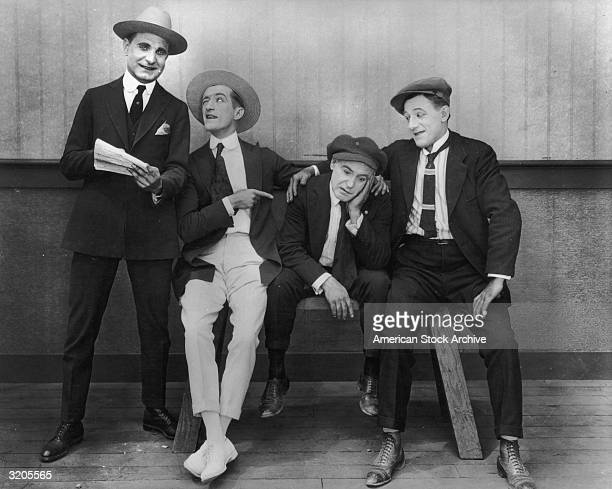Actors left to right William McCall and Hugh Fay try to cheer up their friend Billy Franey as an unidentified actor looks on in a silent comedy film...