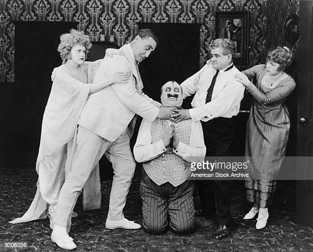 American actor Mack Swain begs on his knees as two men on either side attempt to strangle him in a silent film still Two women try to restrain the men