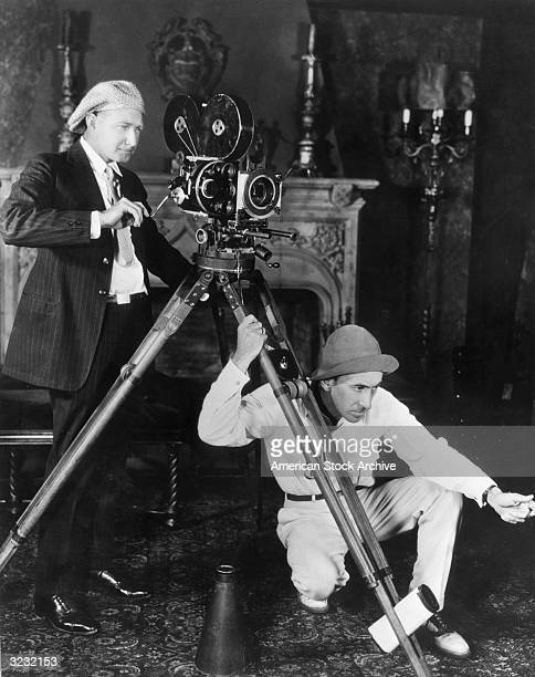 American film producer and director William C DeMille crouching down and holding onto the leg of a motion picture camera tripod gestures as...
