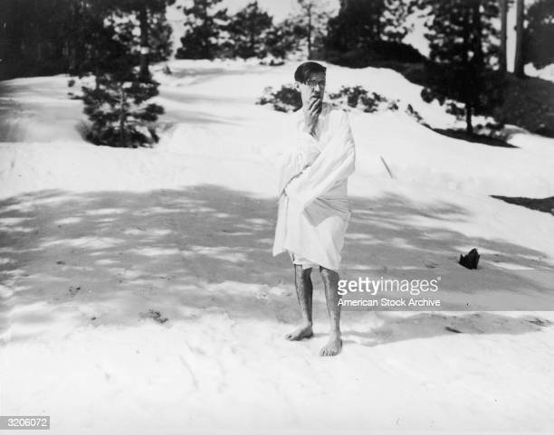 American silent film comedian Charley Chase stands on a snowcovered slope wrapped in a sheet with his hand to his chin