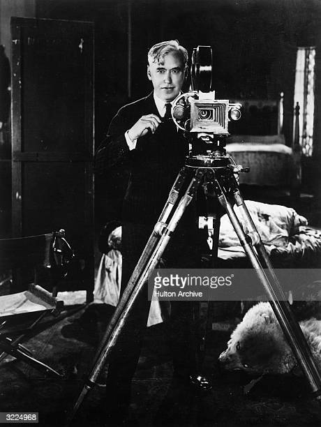 Canadianborn film director Mack Sennett standing behind a handcranked movie camera on the set of a film
