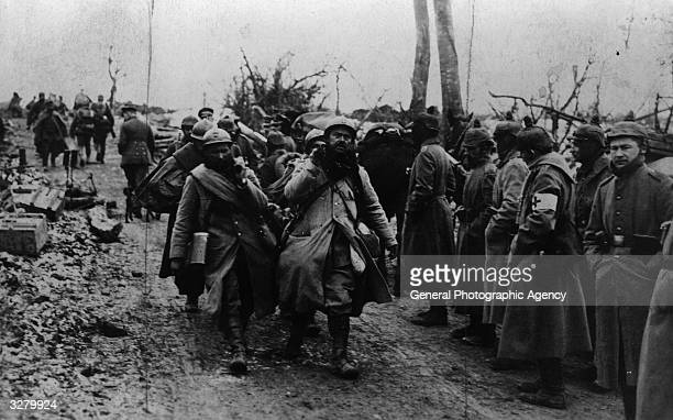 Captured French soldiers carrying their wounded comrades