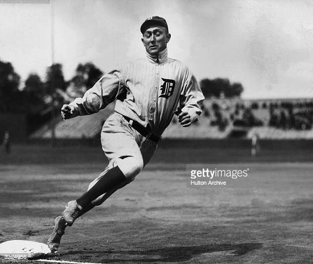 Full-length image of Detroit outfielder Ty Cobb touching third base while running during a baseball game.