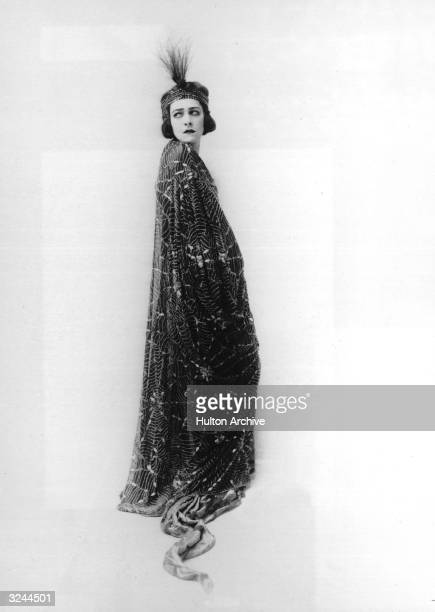 Fulllength promotional studio portrait of Russianborn actor Alla Nazimova wearing a robe with a spider web motif 1910s