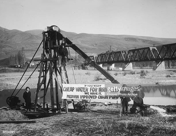 Fulllength view of salesmen and boosters demonstrating an irrigation pump near Lewiston Washington A banner reads 'If You Want Cheap Water for...