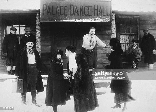 People arrive and leave the Palace Dance Hall in an unidentified film still The hall is covered in snow