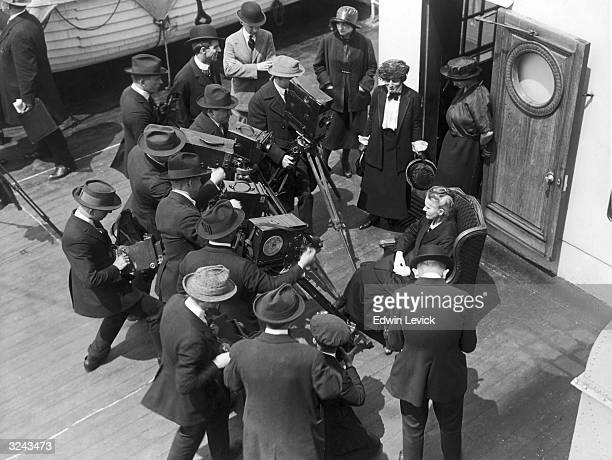 Polish chemist Marie Curie standing in front of a group of cameramen on board a ship