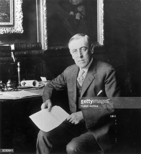Portrait of US president Woodrow Wilson sitting at a desk holding a letter