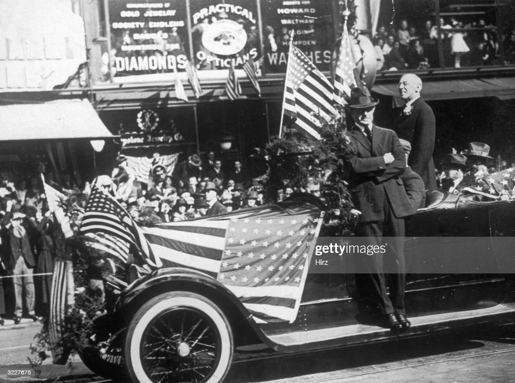 President Woodrow Wilson stands in a car and is cheered by enthusiastic crowds as he passes through the streets of San Francisco, California.