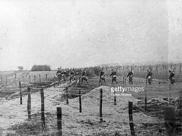 Soldiers make their way across a series of barbed wire defences