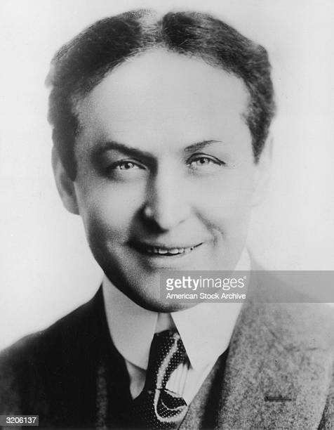 Studio headshot portrait of Hungarianborn magician and escape artist Harry Houdini smiling in a jacket and tie