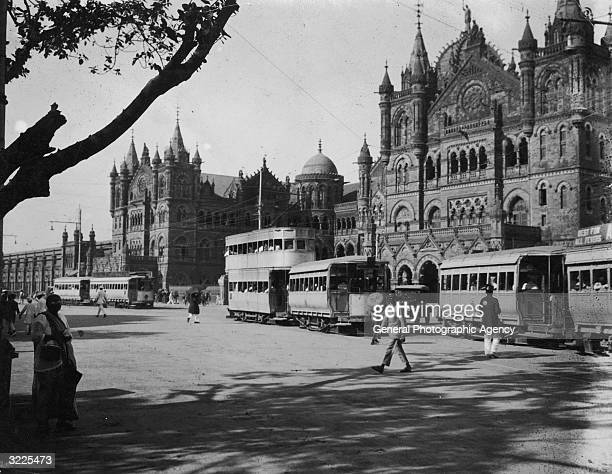 Trams passing the grand facade of Victoria Railway Station in Bombay.