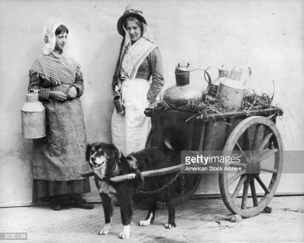 Two young milkmaids wearing aprons bonnets and shawls tucked into their skirts as they stand beside a dogdrawn cart laden with straw and milk pails...