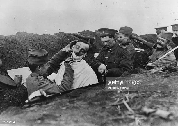 A soldier gets a shave in a Serbian trench