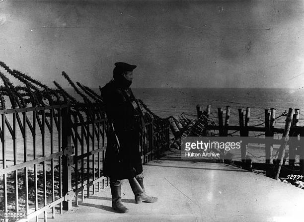 An armed German soldier stands watch on the fortified seawall at Helgoland