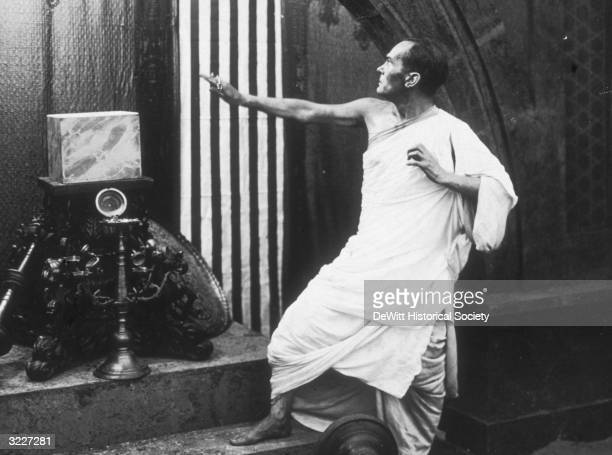 An unidentified actor wearing a Roman toga and pointing towards a barred window in a film still