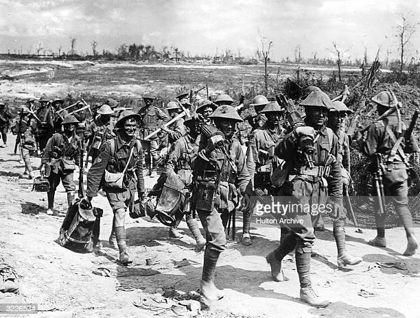 Australian machine gunners marching on a dirt road back from the front line trenches towards their billets France World War I They pass other troops...