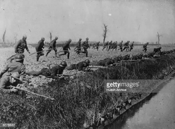 Belgian soldiers rush to commence battle on the banks of a canal near Ypres