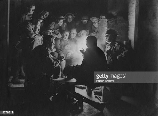 British soldiers sitting around a lamp in their trench.