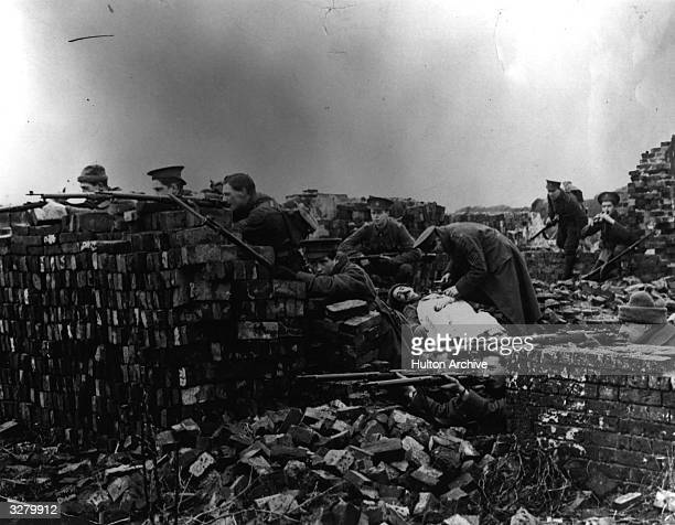 British troops in France during WW1 firing from behind ruins whilst an injured comrade is tended to