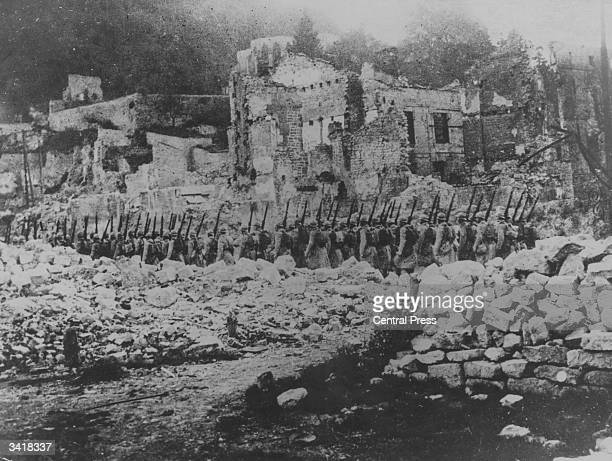 French soldiers pass through a bombed out area as they advance on the Somme
